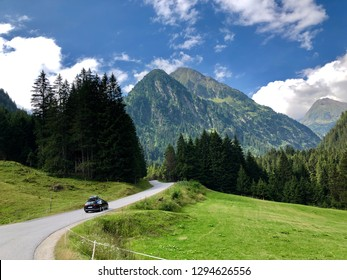 A car driving through beautiful road with big mountains on Neustift im Stubaital road in Austria