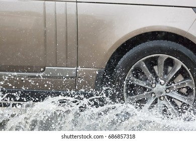 Car driving through a puddle on a flooded road with water and splashes caused by heavy rain