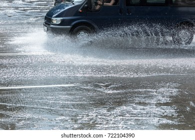 car driving through puddles creating splashes of rainwater around