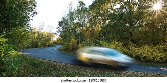 Car driving through a rural road in autumn