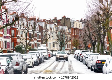 Car driving through a terraced street covered with snow around West Hampstead area in London while snowing and sleeting
