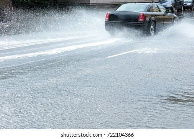 car driving  through water puddles on flooded city road