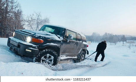 Car driving through a winter storm with snow on a forested road. Black SUV  sticks in deep snow slips.