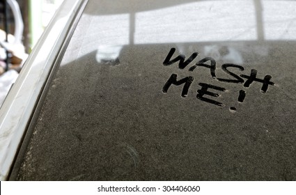 "Car dust with inscription ""WASH ME!"" word on a dirty glass window, front view."