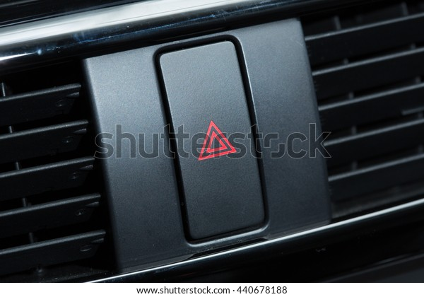 Car emergency attention light button in red triangle