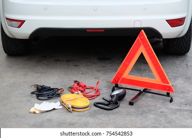 Car emergency kit, Battery Jumper cable, Tow cable, flashlight, gloves, hazard triangle warning sign.