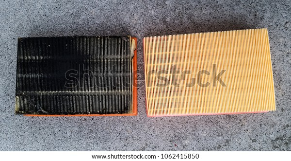 Car engine filters laying side by side, old verses new