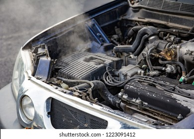 Car engine over heat with no water in radiator and cooling system.Overheated car machine Broken down with smoking, overheating engine on the road.Automotive motor problem concept.