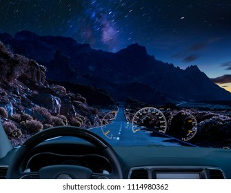 car equipped with a HUD display driving at night along a mountain road near a volcano