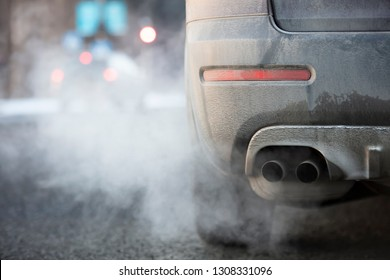 Car exhaust pipe, which comes out strongly exhaust gases in Finland. It is winter and the car is very dirty.
