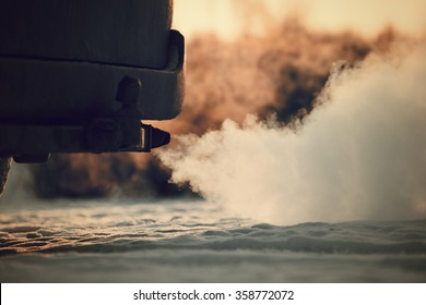Car exhaust pipe, which comes out strongly of smoke in Finland. Focal point is the exhaust pipe. Background out of focus. Image includes a vintage effect.