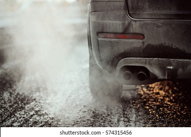 Car exhaust pipe, which comes out strongly exhaust gases in Finland. It is winter and the car is very dirty. Image includes a effect.