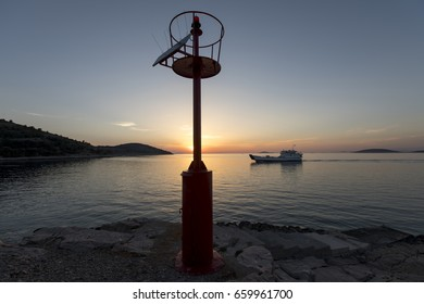 car ferry in the background of solar powered beacon near the port of muna on the island zirje in croatia