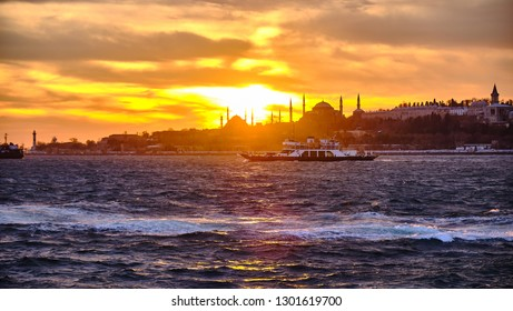 Car ferry navigating on the bosphorus river at sunset, with Sultanahmet profile in background, Istanbul Turkey - December 24, 2018