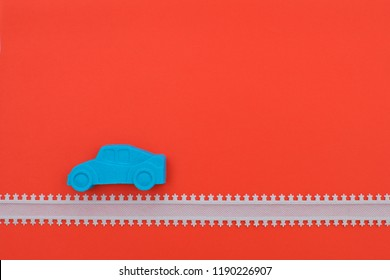 car figure made of magic sand on red background