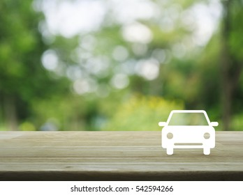 Car flat icon on wooden table over blur green tree background, Business service car concept