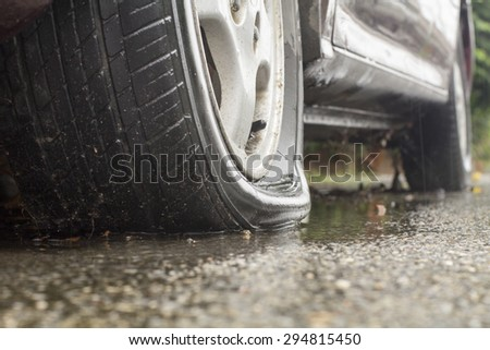 Car flat tire in rainy day