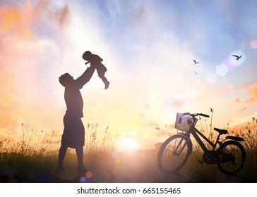 Car free day concept: Silhouette 	 father throwing son into sky on meadow sunset with bicycle background