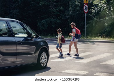 Car in front of children on pedestrian crossing walking from the school and looking at their smartphones