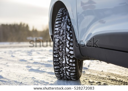 Car front corner, winter tire and the snowy landscape in Finland.