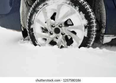 Car front wheel stuck in the white snow in the parking lot