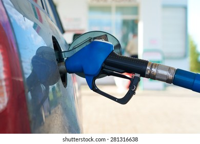 The car is fueled with gasoline at a gas station