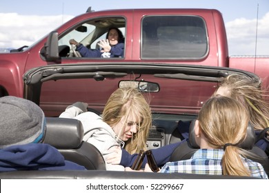 A car full of teens drinking beer and not paying attention to the truck in front of them, with the driver looking in the back for another beer.