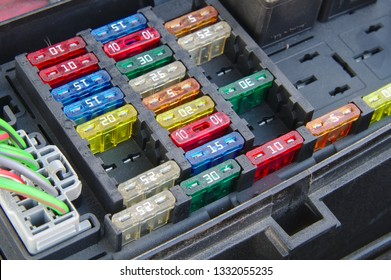 Car fuse box closeup. Multiple rows of different fuses, one connector and part of a relay visible.