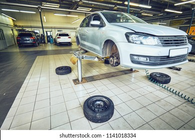 Car in garage, auto repair service shop with special repairing equipment, change tires