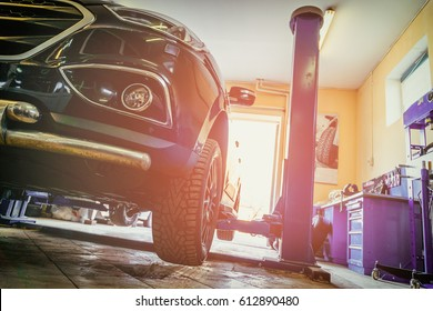 Car in garage of auto repair service shop with special repairing equipment