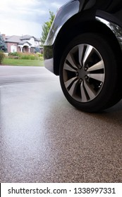 Car in garage with epoxy floor coating over concrete.
