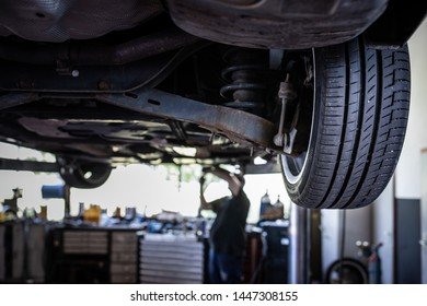 Car in a garage for maintenance, oil/tyre change (shallow DOF; color toned image)