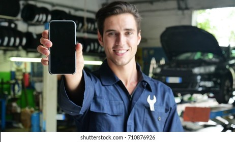In a car garage a mechanic after checking the car smiles showing the phone for getting in touch using the app. Concept of: security, safety, insurance and professionalism, technology and applications.