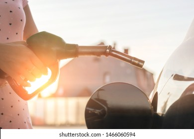 Car gas nozzle refuel fill up with petrol gasoline at a gas station. Close up.  Gas pump nozzle in the fuel tank of bronze car, refuel petroleum to vehicle at gas station.