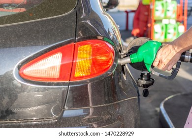 Car gas nozzle refuel fill up with petrol gasoline at a gas station.  Pretty young woman refuel the car. Transportation and ownership concept.