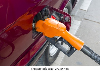 Car at gas station being filled with fuel