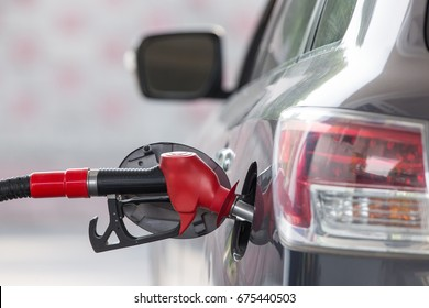 The car at the gas station is refueled with gasoline