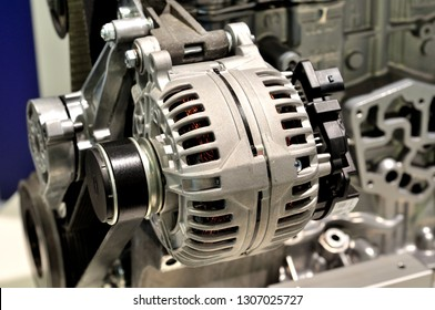 Car generator mounted on an engine, with drive belt.