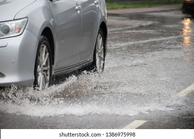 The car goes through a puddle. Puddles on the road. Water from the wheels. Road after the rain. . Russia, Leningrad region, Gatchina July 21, 2018