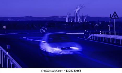 A car going in front of a power station at night