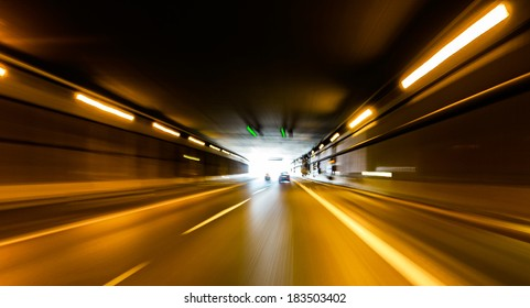 A car going full speed at the end of the tunnel