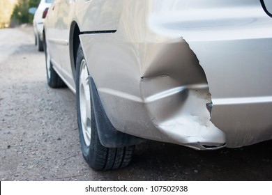 A car has a dented rear bumper after an accident/Damage/Car Accident