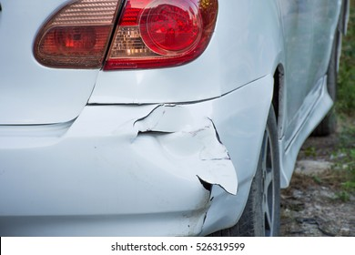 A car has a dented rear bumper