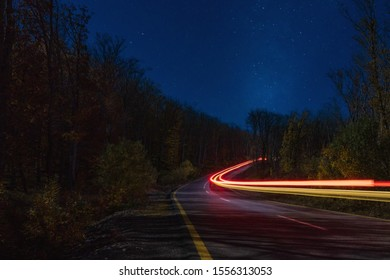 Car headlamp light in night forest