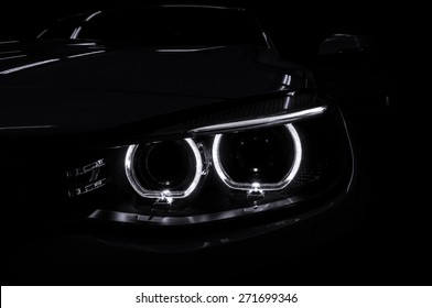 Car headlight with backlight on black background. Exterior detail.