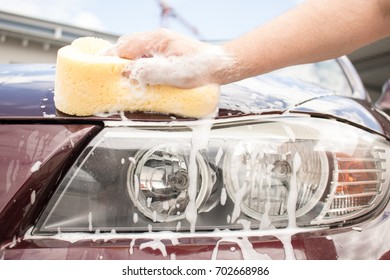 car headlight being cleaned using a sponge