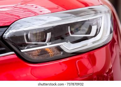 Car headlight close up, lens led light on the red car.