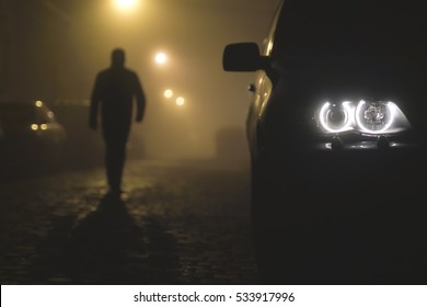 The car headlight on a foggy background with a walking man. Evening-night time