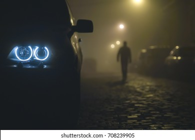 The car headlight with a walking man on the background of a mist