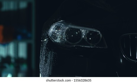 Car headlight wash. Washing modern vehicle body by high pressure jet wash hose water. Auto glass headlamp, angel eyes in drops. Close up of the spotlight of a black automobile as it gets cleaned.